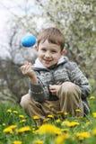 Muchacho con el huevo del eastre entre jardín de la primavera Foto de archivo