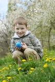 Muchacho con el huevo del eastre entre jardín de la primavera Imagenes de archivo