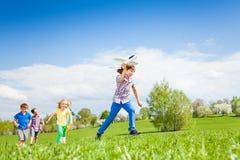 Muchacho con el juguete del aeroplano que corre rápidamente y otros niños Foto de archivo