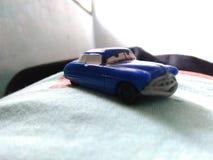 Muchacho con el juguete del coche en cama Foto de archivo libre de regalías