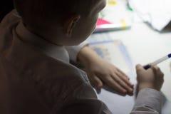 Muchacho con el lápiz que escribe palabras inglesas a mano en el papel blanco tradicional de la libreta Fotografía de archivo libre de regalías