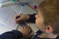 Muchacho con el lápiz que escribe palabras inglesas a mano en el papel blanco tradicional de la libreta Foto de archivo libre de regalías