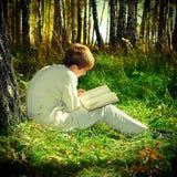 Muchacho con el libro al aire libre Fotos de archivo libres de regalías