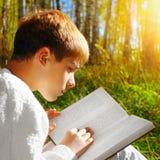 Muchacho con el libro al aire libre Fotos de archivo