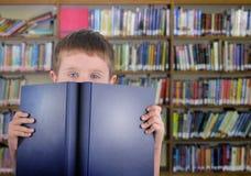 Muchacho con el libro azul en biblioteca Fotografía de archivo libre de regalías