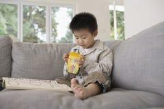 Muchacho con el libro de colorear que se sienta en el sofá Fotos de archivo libres de regalías