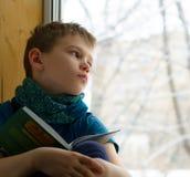 Muchacho con el libro que mira a través de la ventana en día de invierno, dentro Fotografía de archivo