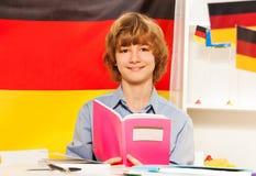 Muchacho con el libro y los colores de la bandera alemana detrás Foto de archivo