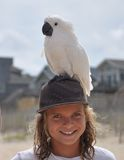 Muchacho con el loro en la cabeza en la playa Imagen de archivo