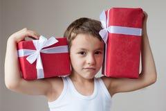 Muchacho con el músculo de la demostración de dos regalos Fotos de archivo libres de regalías