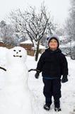 Muchacho con el muñeco de nieve Foto de archivo libre de regalías