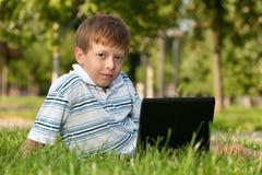 Muchacho con el ordenador portátil en el césped Foto de archivo libre de regalías
