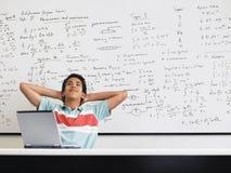 Muchacho con el ordenador portátil que se sienta en sala de clase Imagen de archivo