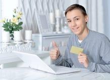 Muchacho con el ordenador portátil y la tarjeta de crédito Fotos de archivo libres de regalías