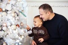 Muchacho con el padre cerca del árbol de navidad Imagen de archivo libre de regalías