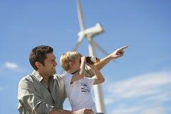Muchacho con el padre At Wind Farm Fotos de archivo libres de regalías