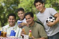 Muchacho (13-15) con el padre y los hermanos en la comida campestre. Imagenes de archivo