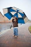 Muchacho con el paraguas en lluvia Fotos de archivo