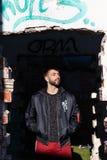 Muchacho con el peinado moderno y barba en un lugar abandonado con ropa casual moderna foto de archivo libre de regalías