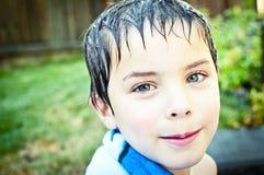 Muchacho con el pelo mojado que sonríe en la cámara Foto de archivo libre de regalías