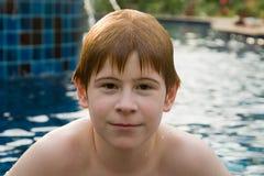 Muchacho con el pelo rojo en piscina Foto de archivo libre de regalías