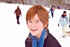 Muchacho con el pelo rojo que goza de la nieve Imágenes de archivo libres de regalías