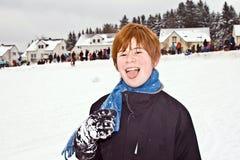 Muchacho con el pelo rojo que goza de la nieve Imagen de archivo libre de regalías