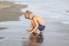 muchacho con el pelo rubio en los vidrios que nadan que juegan en la playa adentro foto de archivo