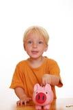 Muchacho con el piggybank Foto de archivo libre de regalías