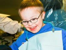 Muchacho con el Plumón-síndrome que se sienta en el dentista Chair Fotografía de archivo
