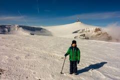 Muchacho con el polo que camina en una trayectoria de la montaña en invierno imagen de archivo