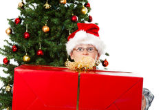 Muchacho con el regalo grande de la Navidad y ojos abiertos de par en par Imágenes de archivo libres de regalías