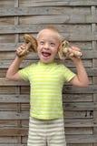 Muchacho con el síndrome hacia abajo que sujeta dos setas anaranjadas Foto de archivo