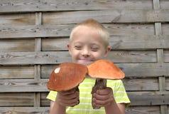 Muchacho con el síndrome hacia abajo que sujeta dos setas anaranjadas Fotos de archivo