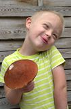 Muchacho con el síndrome hacia abajo que sujeta la seta anaranjada Fotos de archivo libres de regalías