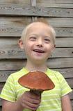 Muchacho con el síndrome hacia abajo que sujeta la seta anaranjada Foto de archivo