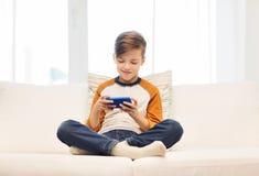Muchacho con el smartphone que manda un SMS o que juega en casa Foto de archivo libre de regalías