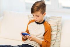 Muchacho con el smartphone que manda un SMS o que juega en casa Foto de archivo
