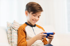 Muchacho con el smartphone que manda un SMS o que juega en casa Fotografía de archivo