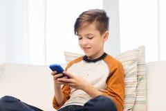 Muchacho con el smartphone que manda un SMS o que juega en casa Fotos de archivo