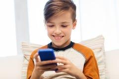 Muchacho con el smartphone que manda un SMS o que juega en casa Fotos de archivo libres de regalías