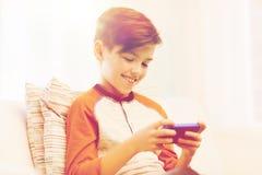 Muchacho con el smartphone que manda un SMS o que juega en casa Imagen de archivo