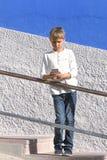 Muchacho con el smartphone que se coloca en las escaleras cerca de la pared colorida Foto de archivo