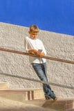 Muchacho con el smartphone que se coloca en las escaleras cerca de la pared colorida Fotos de archivo