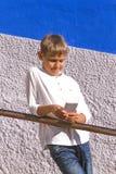 Muchacho con el smartphone que se coloca que se inclina contra la escalera que cerca con barandilla al aire libre Fotografía de archivo libre de regalías