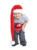 Muchacho con el sombrero de Santa y las decoraciones rojas de la Navidad Foto de archivo