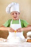 Muchacho con el sombrero del cocinero que prepara la pasta Foto de archivo