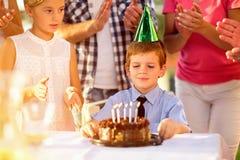 Muchacho con el sombrero del partido y la torta de cumpleaños imagen de archivo