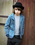 Muchacho con el sombrero que se inclina contra la pared Fotos de archivo