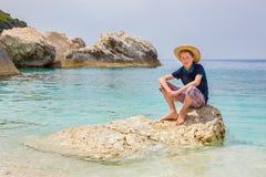 Muchacho con el sombrero que se sienta en roca en el mar Imagenes de archivo